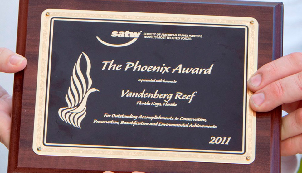 Team members of Reefmakers holding the phoenix award